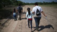Families of Central American immigrants walk through the countryside after crossing from Mexico to the United States to seek asylum on April 14, 2016 in Rome, Texas. Photographer: John Moore / Getty Images
