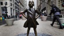 """Ciudadanos observan la escultura """"TheFearlessGirl"""" (lit. La chica valiente) del artista Kristen Visbal, que fue instalada por la empresa State Street Global Advisors frente a la famosa escultura del Toro de Wall Street, con la idea de ver a la mujer en posiciones de liderazgo, en Nueva York (Estados Unidos), el 7 de marzo de 2017. EFE/Justin Lane"""