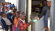 Children in the ultra-impoverished community of Kliptown outside Johannesburg, South Africa receive after-school meals funded by donations. LBWPhoto