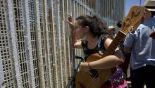 """Una mujer habla con alguien tras la reja que separa la frontera entre México y EE.UU. ayer, sábado 27 de mayo de 2017, durante la décima edición del """"FandangoFronterizo"""", en Tijuana (México).EFE/David Maung"""