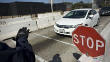 Un agente de la Oficina de Aduanas y Protección Fronteriza (CBP) de EE.UU ordena a un auto que se dirige a México a través del paso deSanYsidro (SanDiego) -Tijuana (México), que pare para una inspección este viernes 28 de abril.EFE/DAVID MAUNG