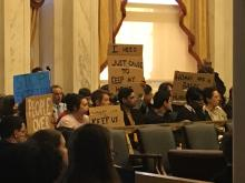 Protesters gather in City Council Chambers.