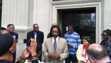 Attorney Michael Coard speaks at April 2017 protest demanding the resignation of DA Seth Williams following Williams' federal corruption indictment. Philadelphia NAACP president Rodney Muhammad (yellow tie) joined others including Mumia Abu-Jamal activist Pam Africa (red tee shirt) and Greg Brinkley (far right) whose investigation ultimately freed a teen in the 911-dialing-dog false arrest. LBWPhoto.