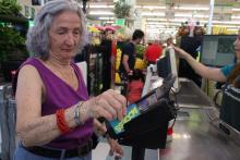 La colombiana Amada Mejía paga su compra en un supermercado de la ciudad de Filadelfiacon su ETB. (Samantha Madera/Al Día News).