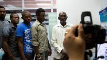 Varios hombres de origen haitiano esperan su turno en el proceso de captura de datos en el Ministerio de Interior y Policía el 17 de junio en Santo Domingo, a unas horas de vencerse el proceso de inscripción al Plan de Regularización de Extranjeros. Quienes no se hayan acogido al Plan, serán repatriados. EFE/Orlando Barría