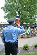 A Philadelphia police officer salutes during the playing of taps at the Living Flame Memorial Service. Photo: Peter Fitzpatrick/AL DIA News