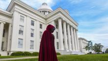 "MONTGOMERY, AL - MAY 19: A protestor dressed as a character from the Hulu TV show ""The Handmaid's Tale,"" based on the best-selling novel by Margaret Atwood, walks back to her car after participating in a rally against one of the nation's most restrictive bans on abortions on May 19, 2019 in Montgomery, Alabama. (Photo by Julie Bennett/Getty Images)"