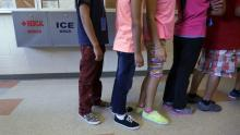 Detained immigrant children line up in the cafeteria at the Karnes County Residential Center, a temporary home for immigrant women and children detained at the border. Eric Gay/AP