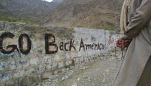 "A man holds prayer beads near a stone wall that reads ""Go Back America"" September 20, 2001, near the Khyber Pass on the Pakistani border with Afghanistan. (Photo by Paula Bronstein/Getty Images)"