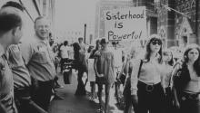 Women marching under a 'Sisterhood is Powerful' placard in the United States, while a group of male workers watch from the left, circa 1975. (Photo by Michael Ochs Archives/Getty Images)