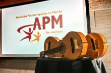 The APM logo is projected on a screen at an event. Image source APM.