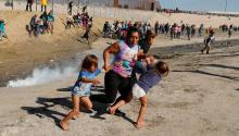 A migrant family runs away from tear gas near the border wall between the U.S and Mexico in Tijuana on Sunday.Kim Kyung-Hoon/Reuters