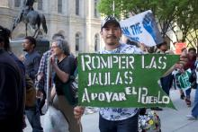"""A man poses with a sign that translates to """"Break the cages, support the people"""" at the Break the Cages, Fund the People May Day rally at Philadelphia City Hall. Photo: Emily Neil /AL DÍA News"""