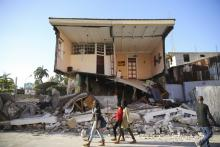 People walk past a home destroyed by the earthquake in Les Cayes, Haiti, Saturday, Aug. 14, 2021. Photo Credit: Joseph Odelyn/AP Photo