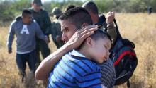 Un padre abraza a su hijo de 3 años mientras duerme, después de haber sido detenido junto a otros inmigrantes indocumentados por la Patrulla Fronteriza el 7 de diciembre de 2015 cerca de Río Grande City (Texas). Foto: John Moore/Getty Images.