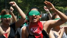 "SANTIAGO, CHILE - DECEMBER 06: Demonstrators wearing green scarves covering their eyes sing and dance in a feminist flash mob that plays ""A Rapist in Your Way"" in protest of violence against women on December 6, 2019 in Santiago, Chile. The song, written by local feminist group Lastesis, is becoming an international feminist phenomenon. (Photo by Marcelo Hernandez/Getty Images)"