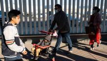 Los solicitantes de asilo que llevan máscaras protectoras caminan hacia su cita con las autoridades de EE.UU. la frontera entre EE.UU. y México en Tijuana, el 29 de febrero de 2020. Guillermo Arias/AFP vía Getty Images