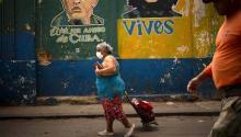 Una mujer, usando una máscara protectora como precaución contra la propagación del nuevo coronavirus, lleva su caddie de compras mientras camina hacia el mercado de La Habana el 24 de marzo de 2020. Ramón Espinosa/AP
