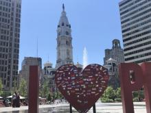 "Participants in the Celebrate Immigrants event placed the flags of various countries on the art installation ""I Love Philly"" on June 4. Photo: Jensen Toussaint / AL DÍA News"