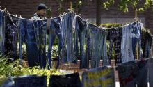LOS ANGELES - APRIL 21: A man watches denim jeans with messages challenging the misconceptions about sexual violence, hung by the UCLA Clothesline Project, on the campus of the University of California in Los Angeles during Denim Day on April 21, 2004, in Los Angeles, California. (Photo by David McNew/Getty Images)