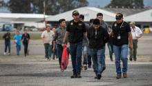 GUATEMALA CITY, GUATEMALA - MAY 30: Guatemalan police escort an accused criminal on the airport tarmac after he and other Guatemalans were deported from the United States on May 30, 2019, in Guatemala City, Guatemala. U.S. Immigration and Customs Enforcement (ICE) charters airplanes to deport some 2,000 people per week to Guatemala from various U.S. cities. (Photo by John Moore/Getty Images)