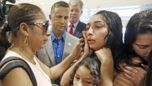 Alejandra Juarez, 39, (L) says goodbye to her children, Pamela and Estela at the Orlando International Airport on Friday, Aug. 3, 2018 in Orlando, Fla. Juarez, the wife of a former Marine is preparing to self-deport to Mexico in a move that would split up their family. (Red Huber/Orlando Sentinel via AP)