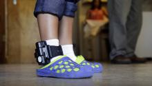 An adult immigrant from El Salvador who entered the country illegally uses an ankle monitor on July 27 at a shelter in San Antonio. Eric Gay/AP