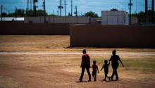 Immigrant women and children walk across a field as Immigration and Customs Enforcement and Enforcement and Removal Operations host a media tour at the South Texas Family Residential Center last summer in Dilley, Texas. Photo: Jabin Botsford/Getty Images.