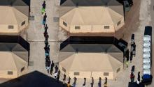 Immigrant children are led by staff in single file between tents at a detention facility next to the Mexican border in Tornillo, Texas, US, June 18, 2018. REUTERS