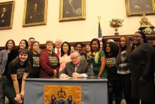 Mayor Jim Kenney (center) signs the Philadelphia Domestic Workers Bill of Rights as domestic workers, organizers, leaders, and elected officials look on. Photo: Emily Neil / AL DÍA News