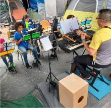 Ernesto Hernandez teaching music lessons to children at Camp Matamoros. Image courtesy of Instagram @ernestohnz.