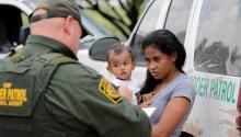 Una mujer hondureña, sosteniendo a su hijo de 1 año, se rinde ante agentes de la Patrulla Fronteriza de los EE.UU. cerca de McAllen, Texas (David J. Phillip/AP)