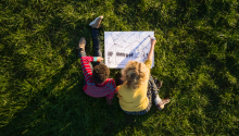Teenage boy and girl on grass experimenting and drawing sustainable energy solutions, overhead view. Photo: Mischa Keijser Getty Images.