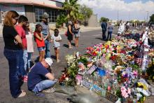 EL PASO, TX: People gather at a makeshift memorial to honor the 22 people who were killed in Walmart during a mass shooting along the U.S.-Mexico border. (Photo by Sandy Huffaker/Getty Images)
