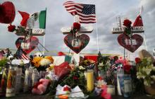 The U.S. and Mexican flags fly above a makeshift memorial for victims outside Walmart, near the scene of a mass shooting which left at least 22 people dead, on August 6, 2019, in El Paso, Texas.President Donald Trump plans to visit the city on August 7. Photo by Mario Tama/Getty Images