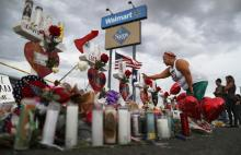 A woman touches a cross at a makeshift memorial for victims outside Walmart, near the scene of a mass shooting which left at least 22 people dead, on August 6, 2019 in El Paso, Texas. A 21-year-old white male suspect remains in custody in El Paso, which sits along the U.S.-Mexico border. President Donald Trump plans to visit the city August 7. (Photo by Mario Tama/Getty Images)