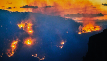 Forest fire, bushfire with flames and smoke in valley at dusk, Blue Mountains, Australia. Getty Images.