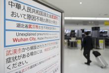 A passenger walks past a notice for passengers from Wuhan, China displayed near a quarantine station at Narita airport on January 17, 2020 in Narita, Japan. Photo: Tomohiro Ohsumi/Getty Images.