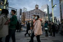 Chinese tourists wearing masks walk through the Ginza shopping district on January 24, 2020 in Tokyo, Japan. (Photo by Tomohiro Ohsumi/Getty Images)