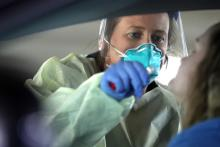 Dawn Canova, clinical manager for outpatient wound care at Carroll Hospital, takes samples from people to test them for the coronavirus at a drive-thru station in the hospital's parking garage. Photo: Getty Images.