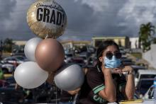 A graduating student from the Ramon Power Y Giralt High School wears a facemask during a symbolic graduation from their cars to maintain social distance at a parking lot in Las Piedras, Puerto Rico, on May 13, 2020. Photo: Ricardo Arduengo/AFP via Getty Images.