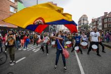 Caption:A woman waves a Colombian national flag during a protest against a tax reform proposed by Colombian President Ivan Duque's government in Bogota, on May 4, 2021. Photo: Juan Barreto/AFP via Getty Images.