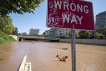 Austin Ferdock drinks a beer while floating in floodwater that continues to rise over the submerged Vine Street Expressway, Interstate 676, following a huge storm caused by the remnants of Hurricane Ida on September 2, 2021 in Philadelphia, Pennsylvania. Photo:Jessica Kourkounis/Getty Images