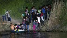 Immigrants prepare to cross the Rio Grande into Texas on August 14, 2021 in Roma, Texas. Recent U.S. Customs and Border Protection figures show more than 200,000 people were apprehended at the border in July, the highest number in 21 years. More than 82,000 of those were family members traveling together.  John Moore/Getty Images