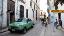 An old car drives past the front of the Rafael Trejo Boxing Gym on May 12, 2015 in Havana, Cuba. (Photo by Ezra Shaw/Getty Images)