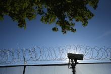 Concertina wire and a security camera line the perimiter of the York County Dentention Center as immigration reform activists protest on September 15, 2015 in York, Pennsylvania. Photo: John Moore/Getty Images.