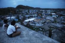 A resident checks her cell phone on her rooftop at dusk about two weeks after Hurricane Maria swept through the island on October 5, 2017 in San Isidro, Puerto Rico. Photo:Mario Tama/Getty Images