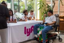 A resident of Nellie Reynolds Gardens, a PHA development, speaks with staffers from Lyft at the kickoff for the Grocery Access Program in Philadelphia. Photo Courtesy of PHA.