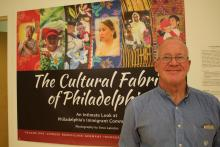 """Photographer Dave Lakatosstands at the gallery exbition of""""The Cultural Fabric of Philadelphia,"""" currently on display at City Hall. Photo: Emily Neil / AL DÍA News"""