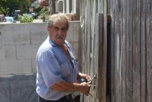 A longtime Norris Square resident, Eddie, opens a fence to one of the lots he's maintained for the last 30 years. Photo: Nigel Thompson/AL DÍA News.